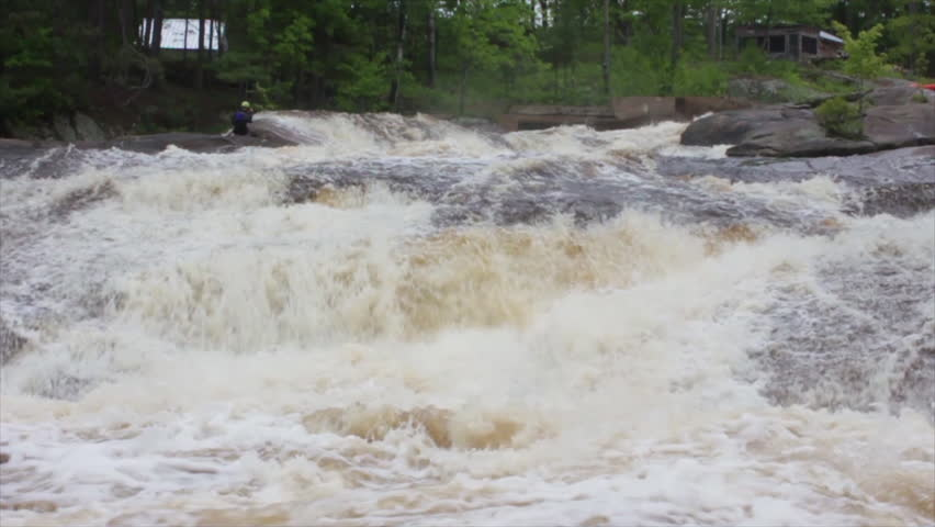 A man in a kayak paddles over white water rapids - HD stock video clip