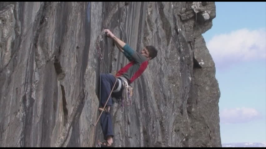 A rock climber climbs up a steep mountain - HD stock footage clip