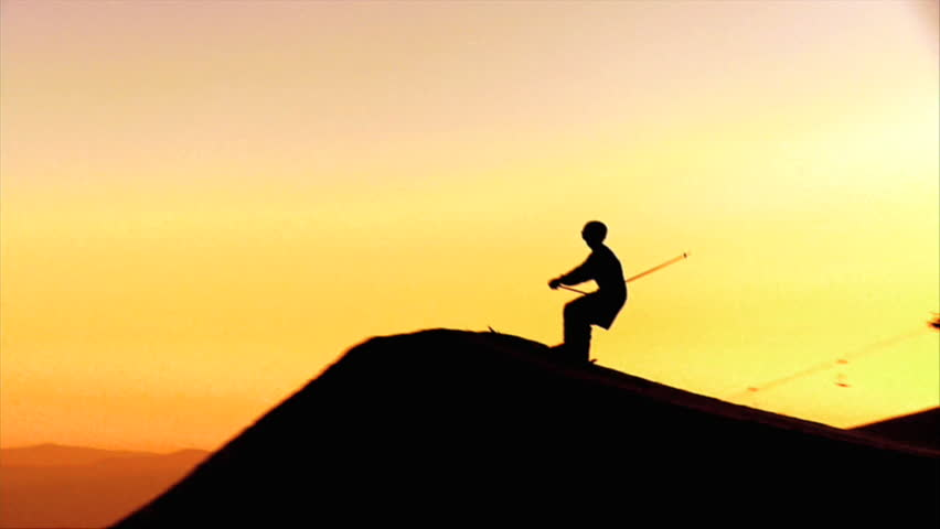Freestyle skier jumps over a kicker in slow motion during an amazing sunset