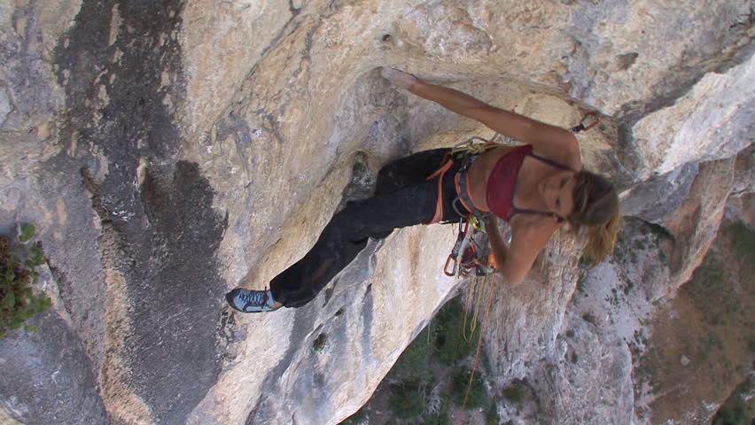 A female climber climbs up a steep rock - HD stock video clip