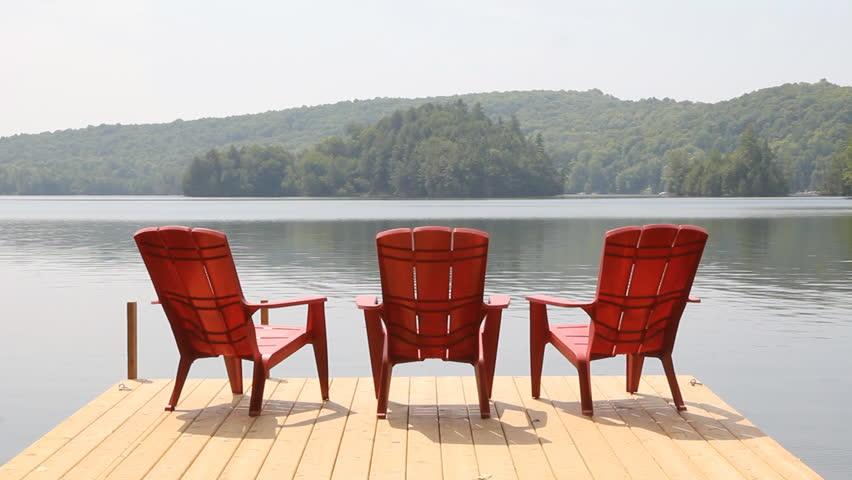Three red chairs on dock. Sunny morning.  Three red chairs on a floating wooden dock. Sunny morning near Haliburton, Ontario, Canada.