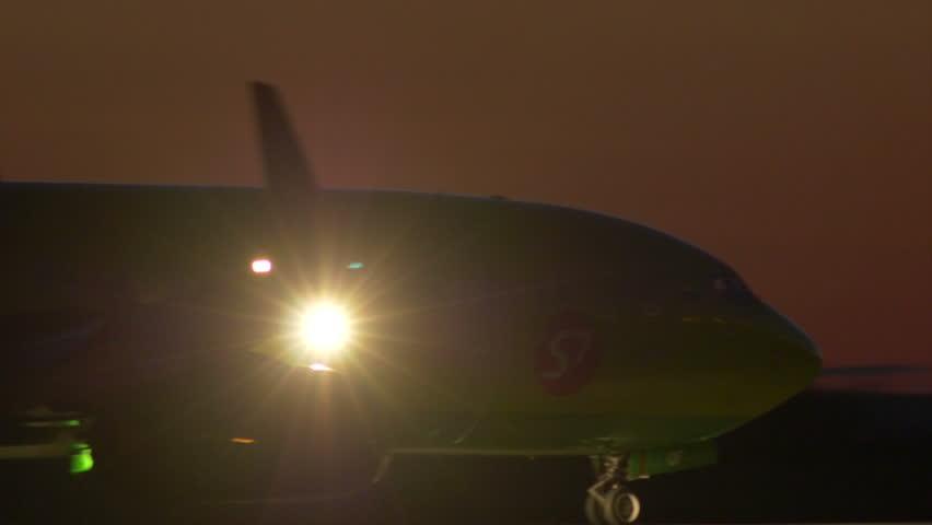 "NOVOSIBIRSK, RUSSIA – AUGUST 9, 2014: Passenger Plane Landing at Night in the  ""Tolmachevo"" airport"