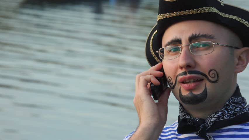 man in pirate costume is speaking on the phone, boat with people behind  - HD stock video clip