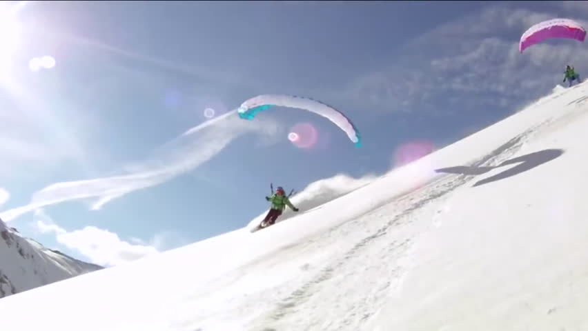Various riders speed riding down a snowy mountain slope