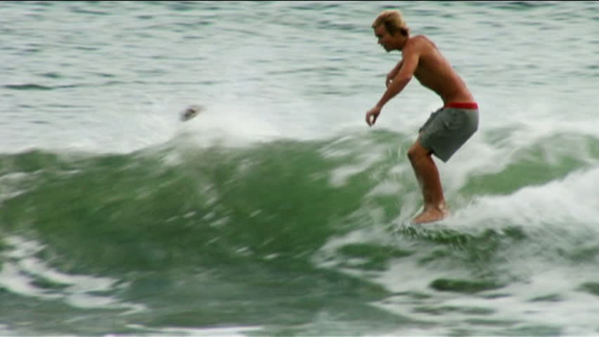 A surfer sits on his surfboard before nose riding a wave, passes other surfers surfing around him - HD stock video clip