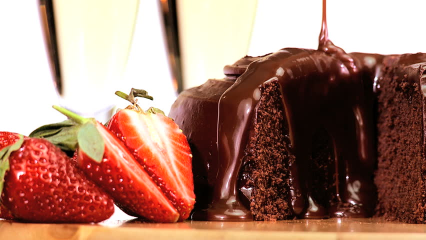 Sticky chocolate cake being covered in sauce while served with fresh strawberries & sparkling white wine - HD stock video clip