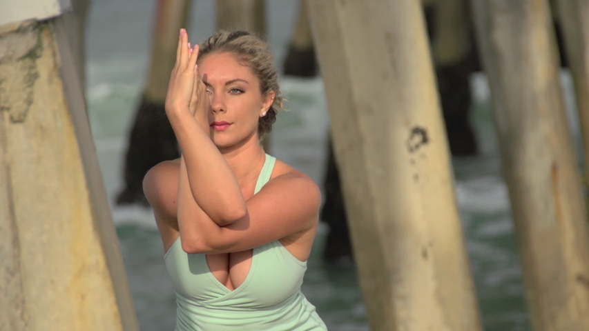 A young attractive woman doing yoga on the beach. - Slow Motion - 1920x1080 - filmed at 59.94 fps | Shutterstock HD Video #7120420