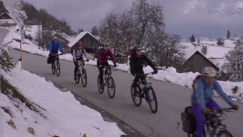 Mountain road through the winter village. Icicles on the tree. Cyclists drive on the road | Shutterstock HD Video #7125280