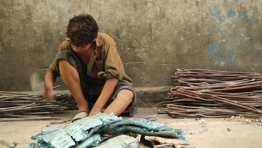 PAKISTAN - GUJRANWALA 2014: A child separating copper pipes from car radiators with the help of sharp hammer in Gujranwala, Pakistan 2014