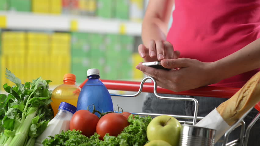 Woman using mobile phone at supermarket hands close-up. - HD stock footage clip