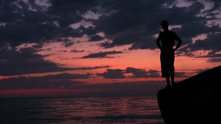 silhouette of young man stands on rock against sunset sky and sea  - HD stock footage clip