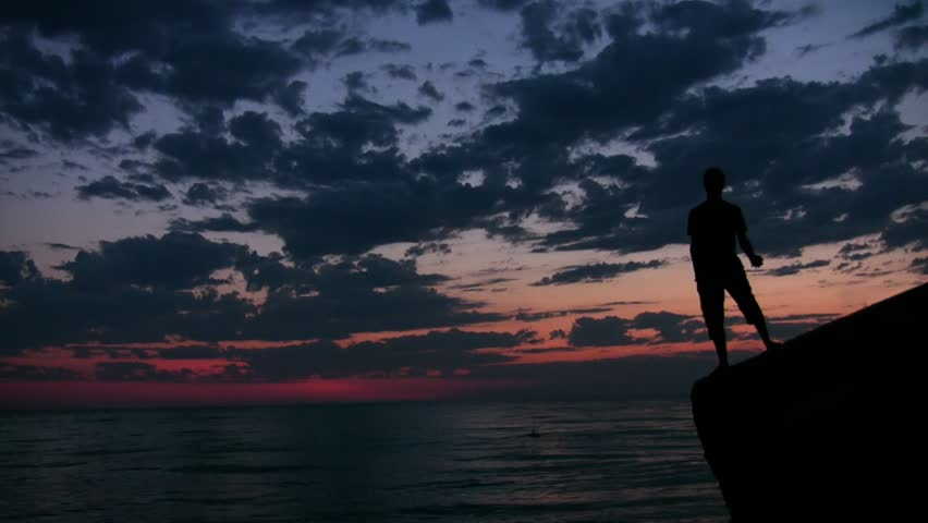 young man stands on rock and throws pebbles into sea under sunset sky  - HD stock footage clip