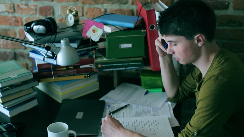 Student doing homework and chatting on cellphone at home  - HD stock video clip
