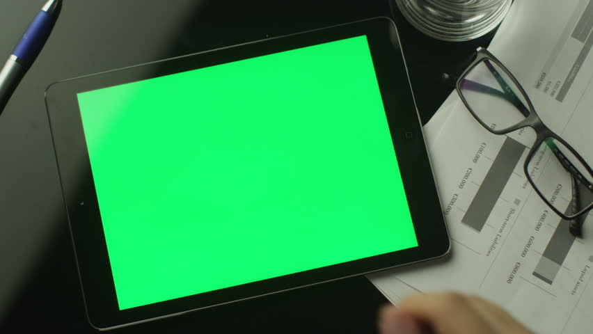 Businessman Using Tablet PC with Green Screen which Lying on the Table. Top view.