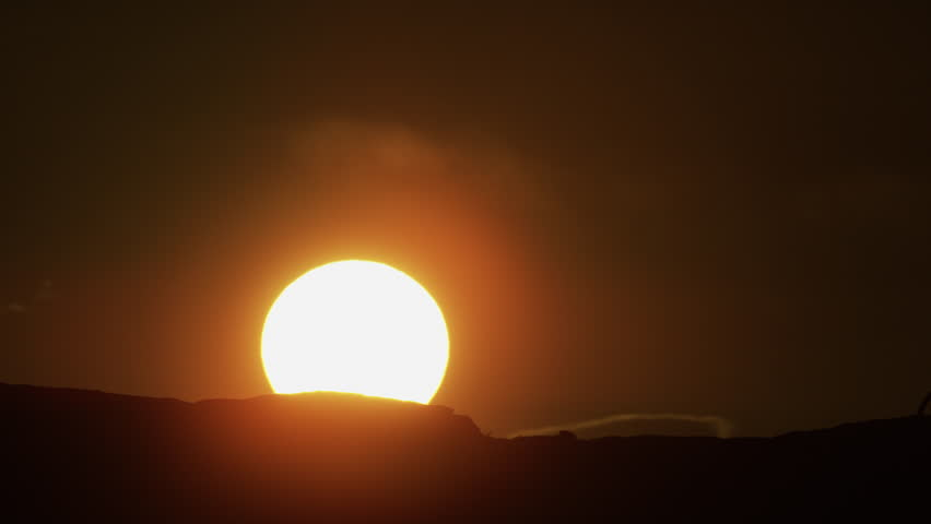 Slow motion wide shot of women biking at sunset / Moab, Utah, United States
