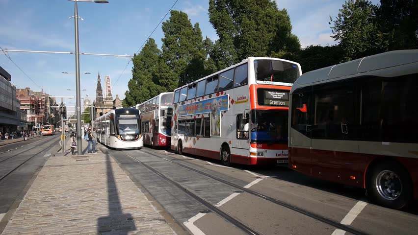 EDINBURGH, SCOTLAND - AUGUST 27,2014: A passenger tram moves away from a stop alongside a number of buses in Princes Street on August 27, 2014 in Edinburgh.