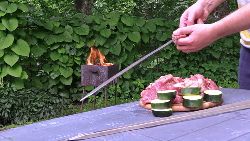 man hand preparing shashlik and zucchini slices on metal skewer. Nice smoulder grill fire in background garden. Shot on Canon XA25. Full HD 1080p. Progressive scan 25fps. Tripod. - HD stock footage clip