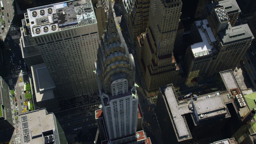 Aerial view of the Chrysler building in New York City. Famous iconic skyscraper towers over NYC. Helicopter shot circling the landmark building.