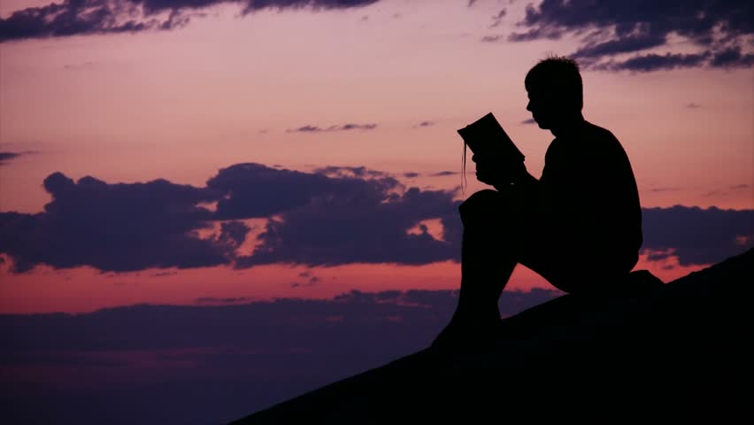 silhouette of boy sitting against sunset sky and reads book, time lapse   - HD stock video clip