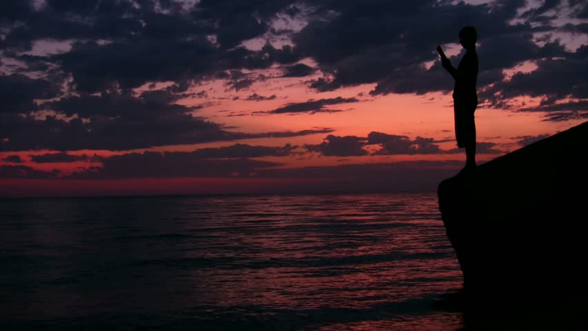 teenager stands on rock above sunset sea and reads book  - HD stock footage clip