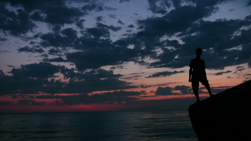 raising hands youngster stands on rock against sunset sky and sea  - HD stock footage clip