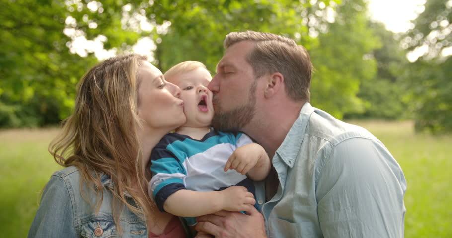 Mom and Dad Kiss Boy on Both Cheeks