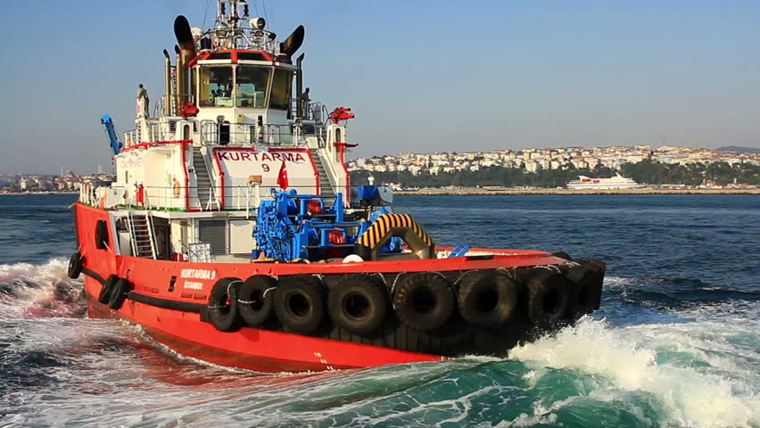 ISTANBUL - JUL 28, 2014: Ship handling and fire boat Kurtarma 9 sails in full speed into Bosporus Sea. Tug is equipped for fire fighting and has a self protection spray system around the structure.