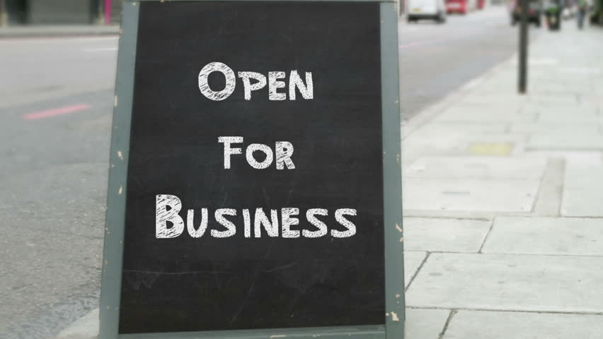 39 open 39 sign is turned to 39 closed 39 in a storefront window for Opening a storefront business