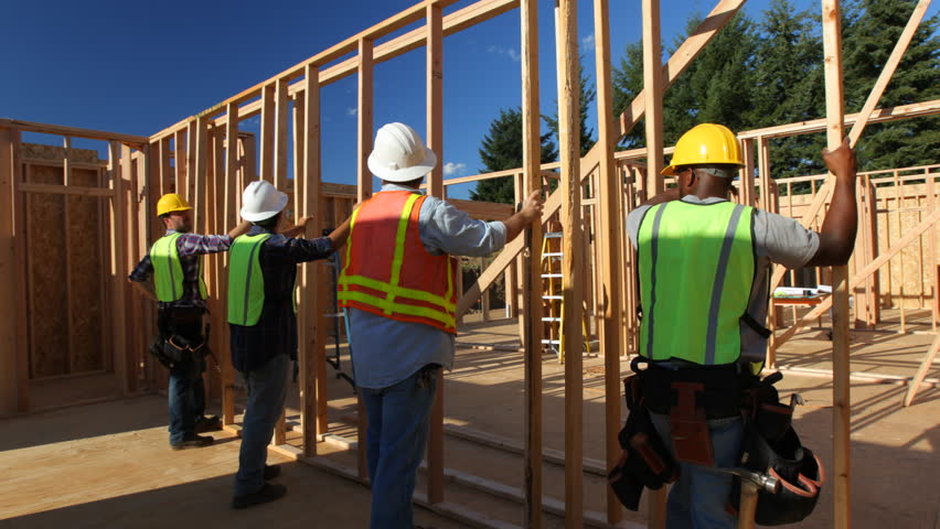 Group of construction workers standing up wall
