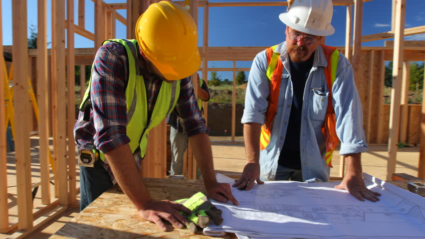 Construction workers looking over plans together stock for My contractors plan