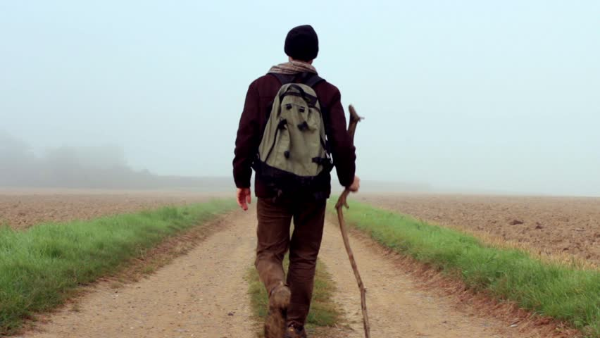 A Traveler With A Walking Stick Journeys Out Of The Mist ... Stick Man Walking Away
