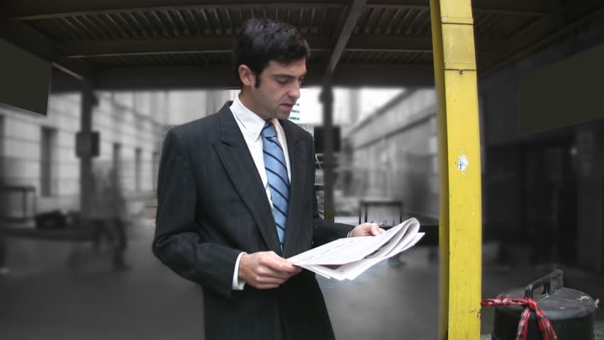 Man reads newspaper. Timelapse commuters in background.