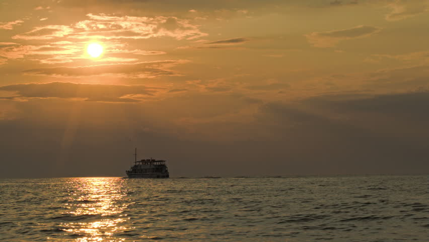 Sailing small ship in quiet open sea at sunset. Water sparkling in dim sunlight | Shutterstock HD Video #7369504