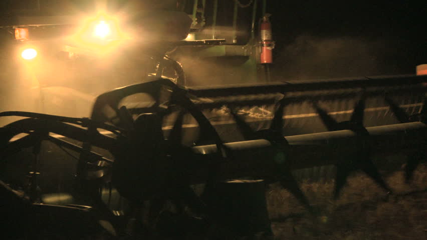 Wheat harvesting with a combine harvester at night  - HD stock video clip