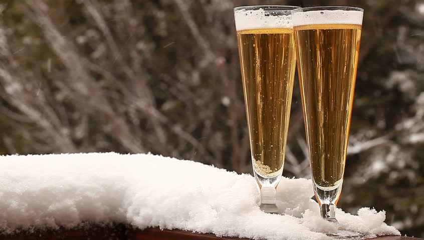 two glasses of beer outside on a deck with snow falling in the background - HD stock video clip