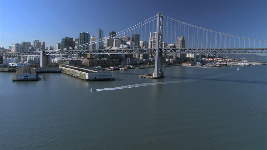 Low aerial view of Oakland Bay Bridge & skyscrapers of San Francisco, USA - HD stock footage clip