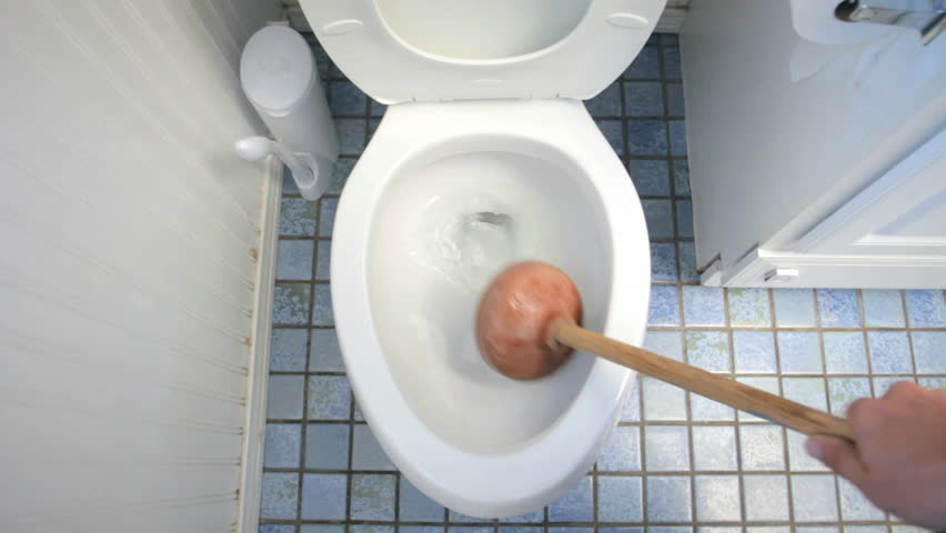 Using plunger for clogged toilet in bathroom