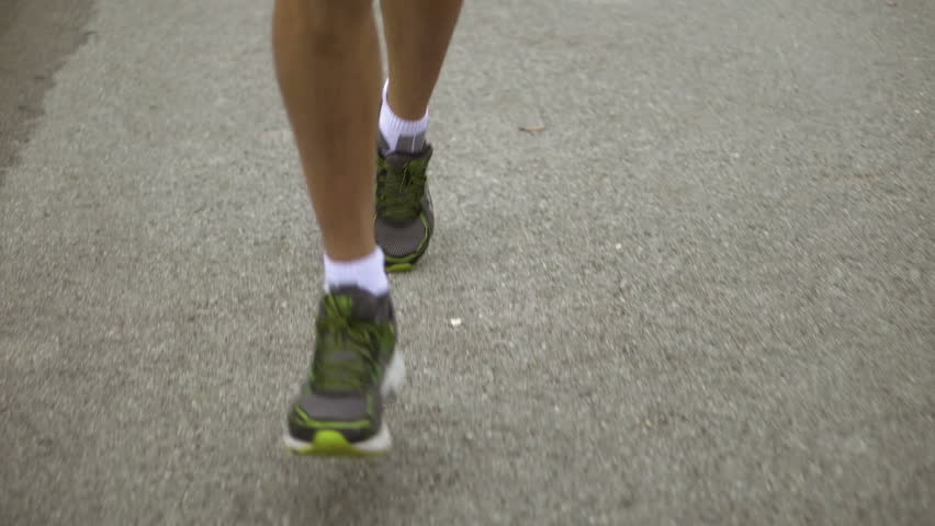 slow motion detail male running legs on asphalt road