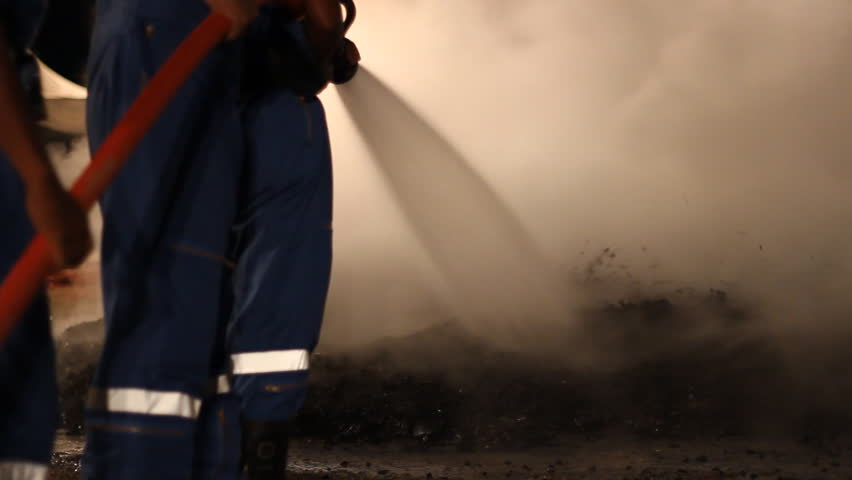 A team of fire fighters hold a hose and put out a house fire