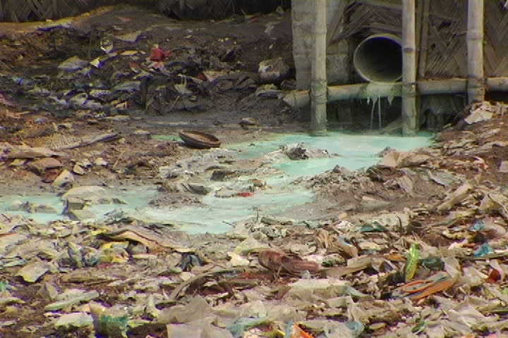 Green, toxic sewage pours out of a drain in a Bangladesh slum. - SD stock footage clip
