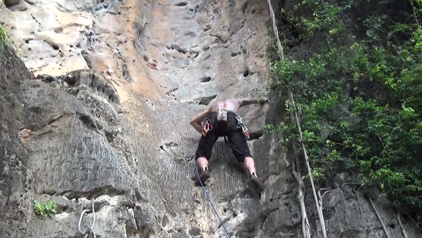 A rock climber adjusts the grip and footing while climbing up a rock formation, attaches a hook into the wall before climbing again, low angle, zoom in - HD stock video clip
