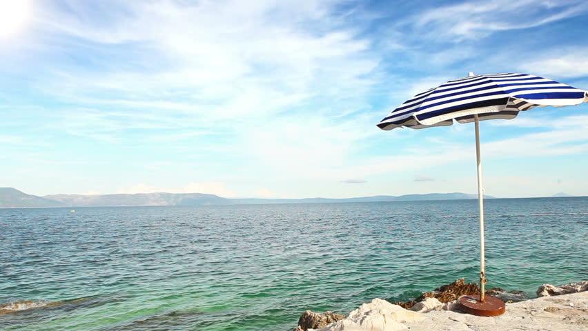 Alone beach retro style umbrella on the croatian shore - HD stock video clip