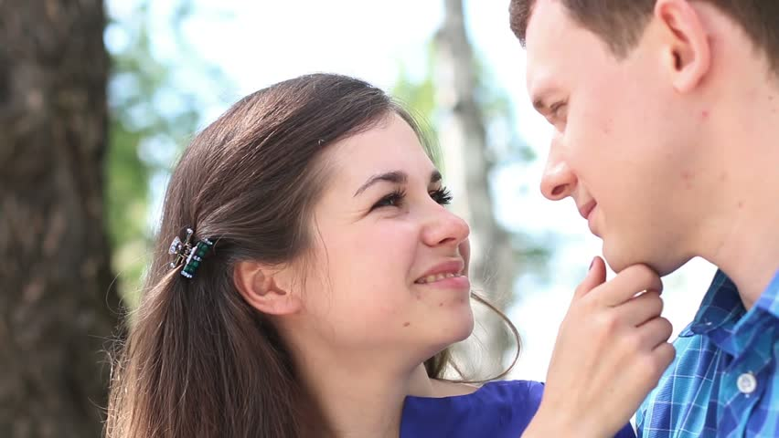 Happy woman looks at young man and kisses him outdoor