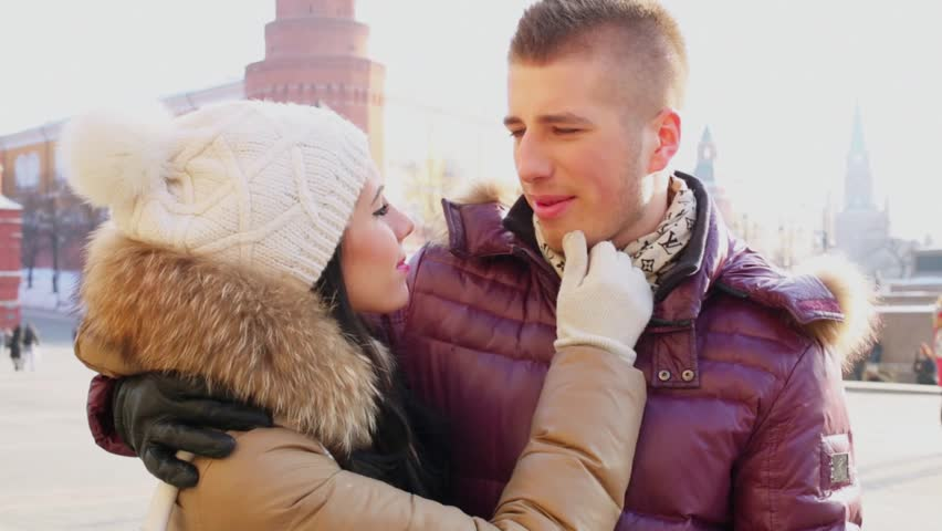 Young man and woman talk and smile near Kremlin complex at Manezhnaya square in Moscow - HD stock video clip