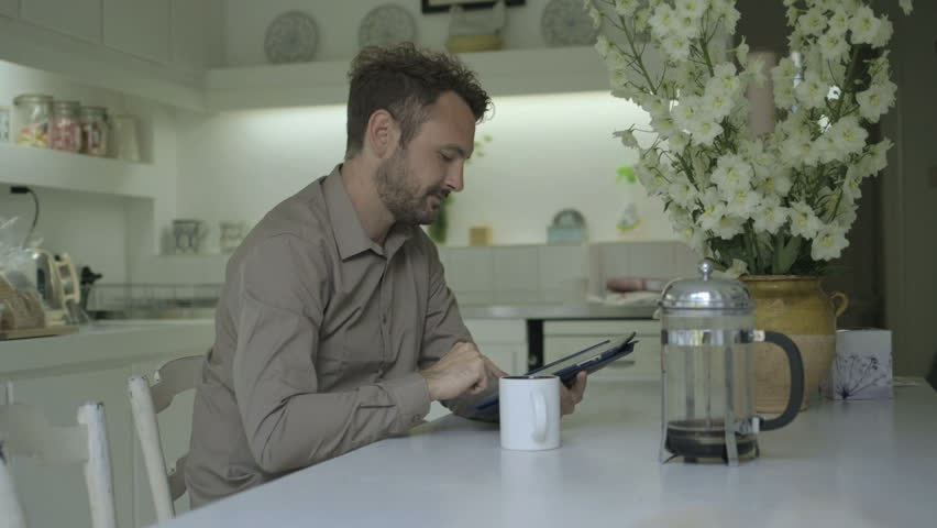 Man using digital tablet while drinking coffee - HD stock video clip