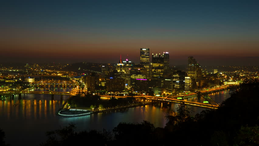(Time-lapse) Morning twilight transitions to sunrise over Pittsburgh, Pennsylvania including the skyline, bridges, and Point State Park at the confluence of the Allegheny and Monongahela Rivers. - 4K stock footage clip