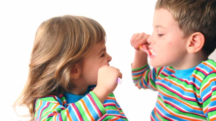 boy and girl brush teeth looking against each other, then turn and smile  - HD stock footage clip
