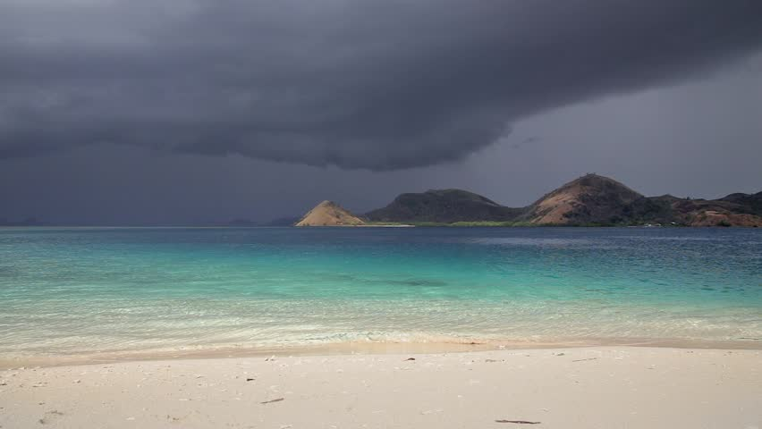 Storm clouds over tropical island. Traditional Komodo tour from Labuan Bajo by boat. Beautiful ocean landscape with turquoise water. Komodo National Park - paradise for diving and exploring.  | Shutterstock HD Video #7516033