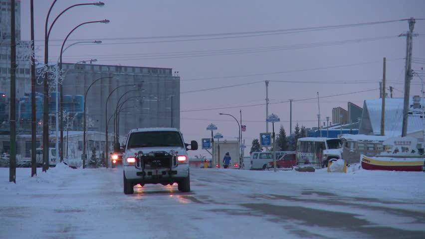 CHURCHILL, MANITOBA, CANADA - CIRCA 2014 - Vehicles travel along an icy snowy road at Churchill, Manitoba, Canada, Hudson Bay.