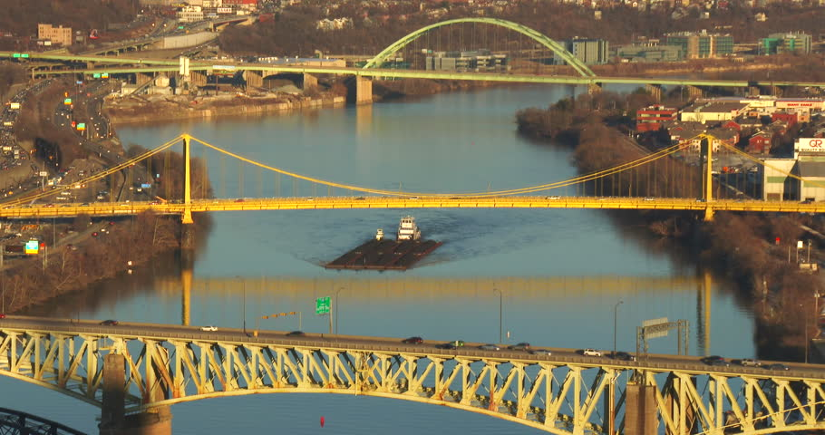 Barges travel under the bridges of Pittsburgh, PA. - 4K stock video clip